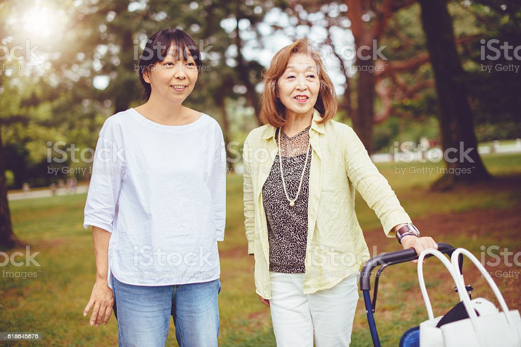 Two Japanese women, senior and mature, relaxing in park stock photo