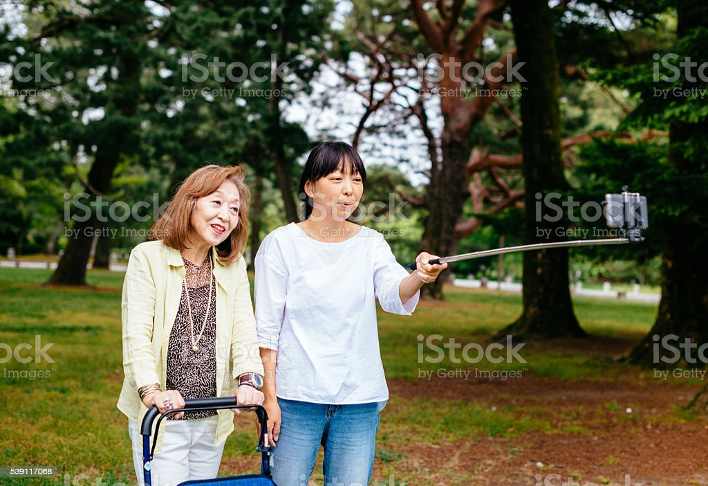 Two Japanese women, senior and mature, taking selfie outdoors stock photo