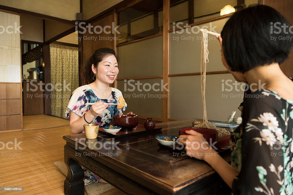 Two Japanese women sitting at table eating food stock photo