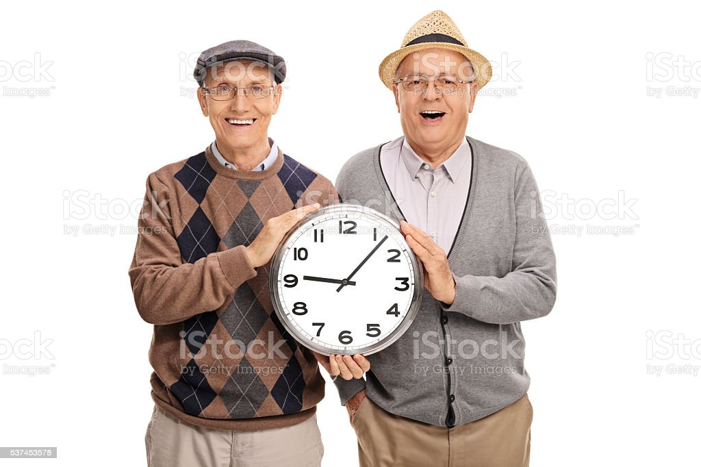 Two joyful elderly men holding a big clock stock photo