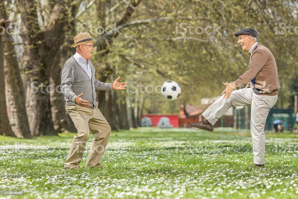 Two joyful seniors playing football in a park stock photo