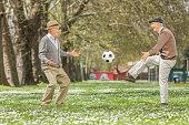 Two joyful seniors playing football in a park