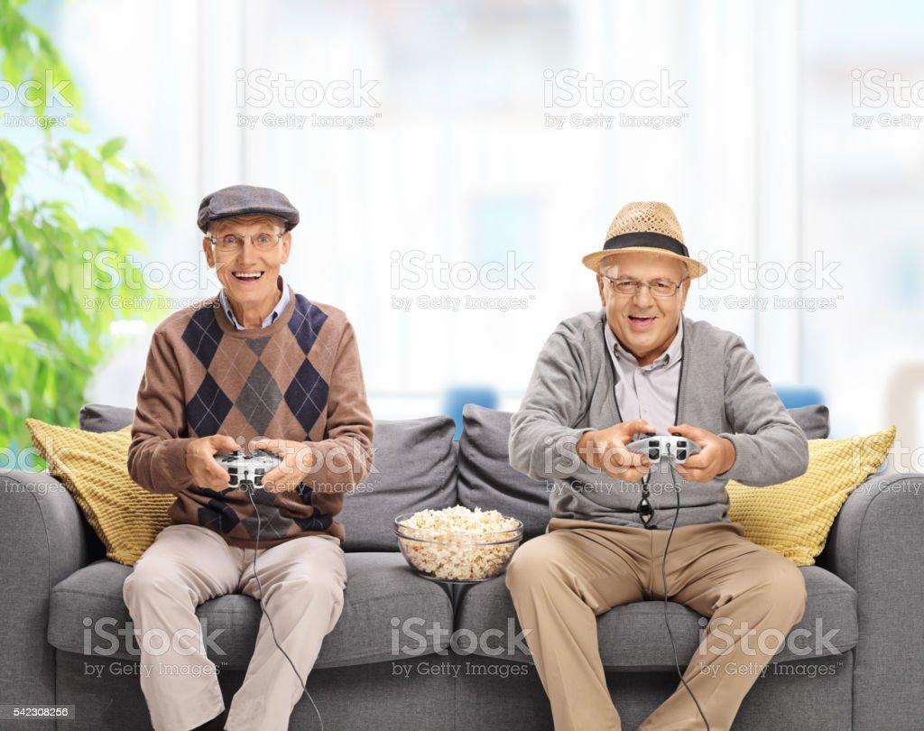 Two joyful seniors playing video games stock photo