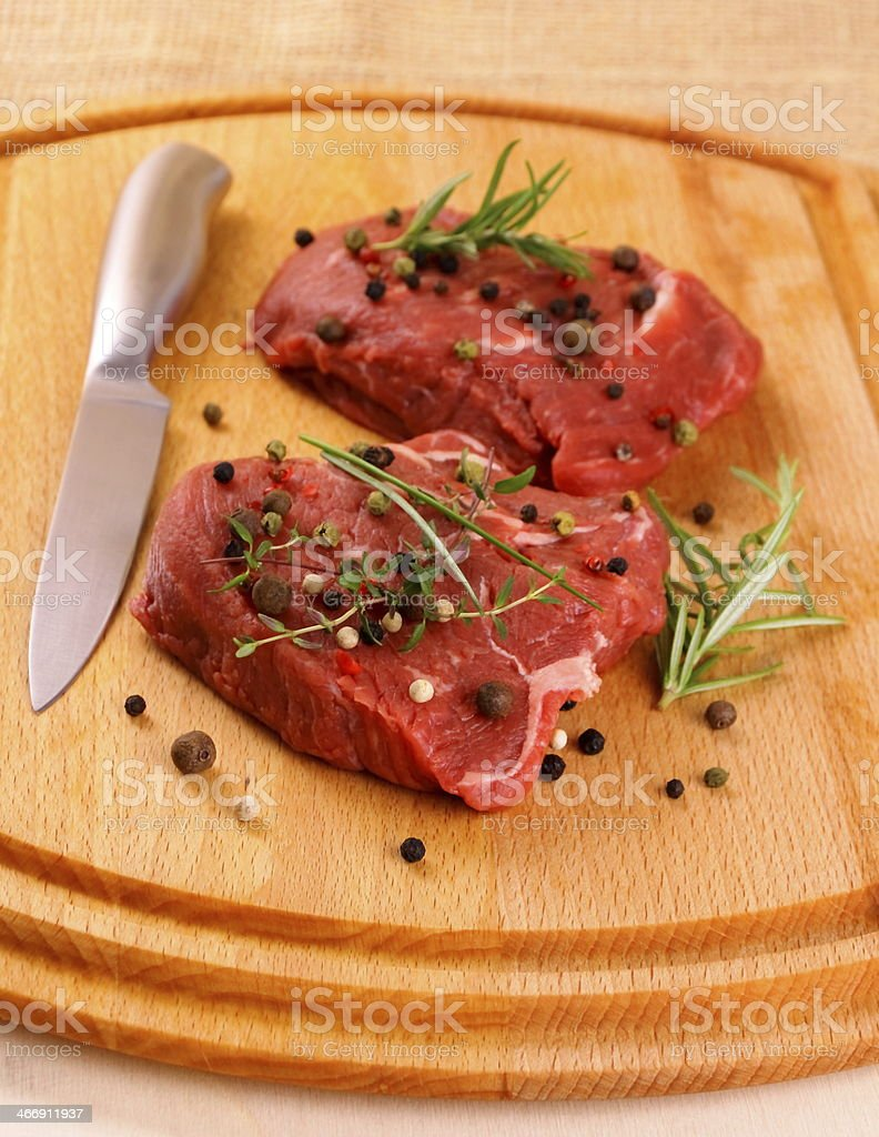 Two juicy beef steak with spices and knife royalty-free stock photo