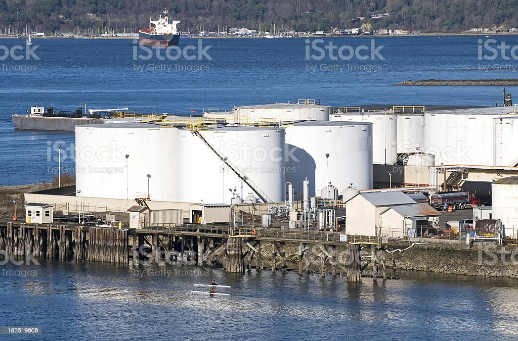 Two kayakers near oil tanks at pulp mill royalty-free stock photo