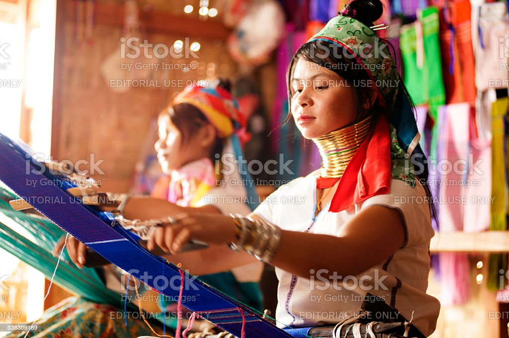 Two Kayan Lahwi girls are weaving. stock photo