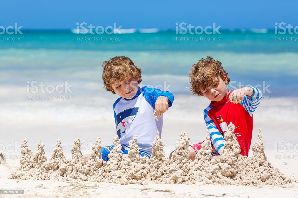 Two kid boys building sand castle on tropical beach stock photo