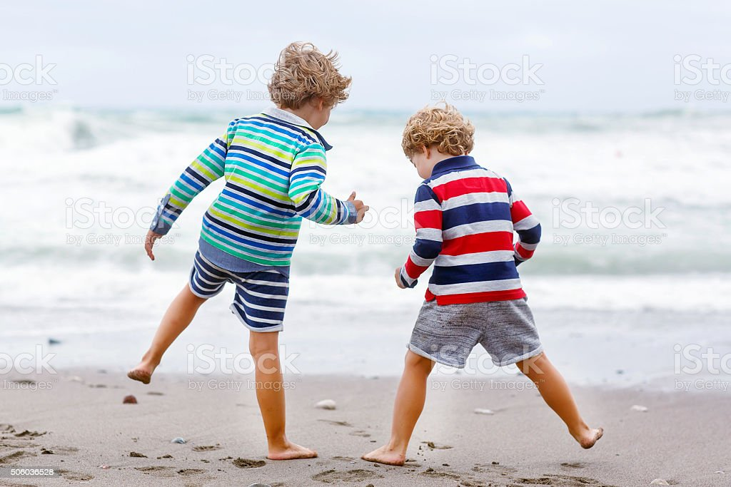 Two kid boys playing on beach on stormy day stock photo