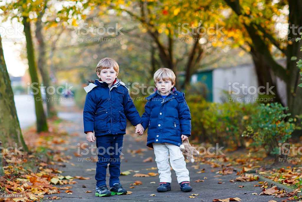 two kid boys walking together in autumn park stock photo