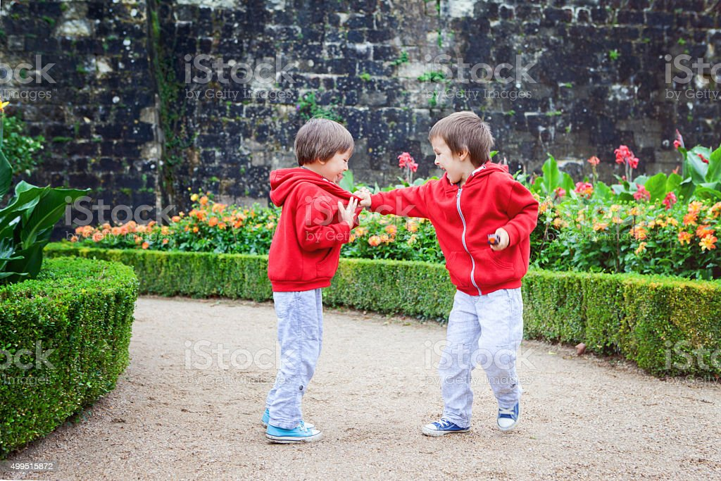 Two kids, boy brothers, fighting in garden, summer stock photo