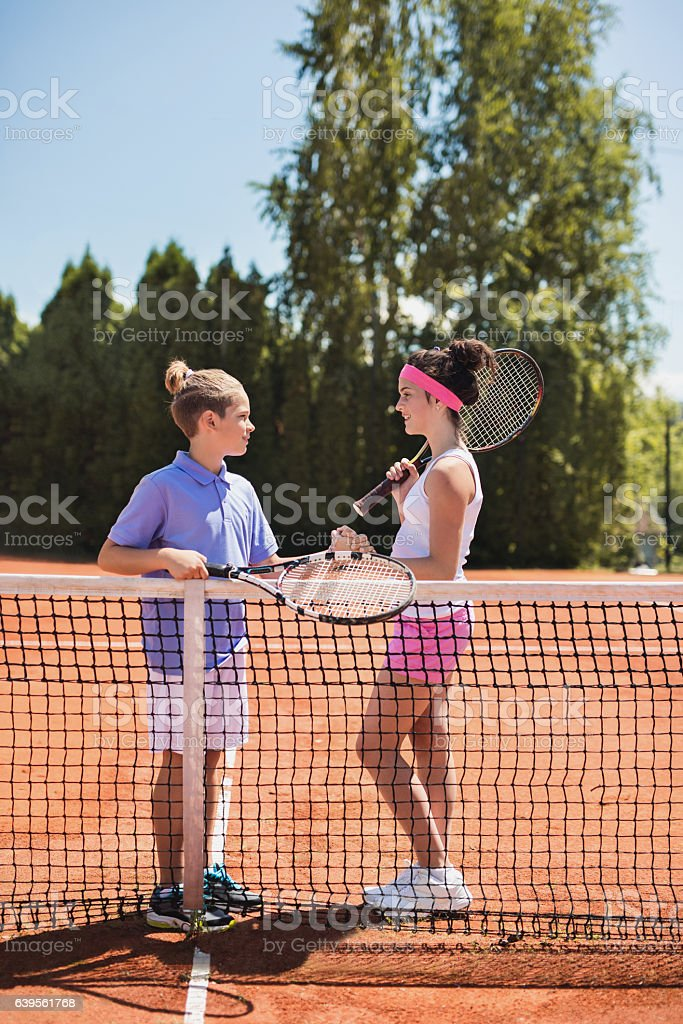 Two kids by tennis net talking to each other. stock photo