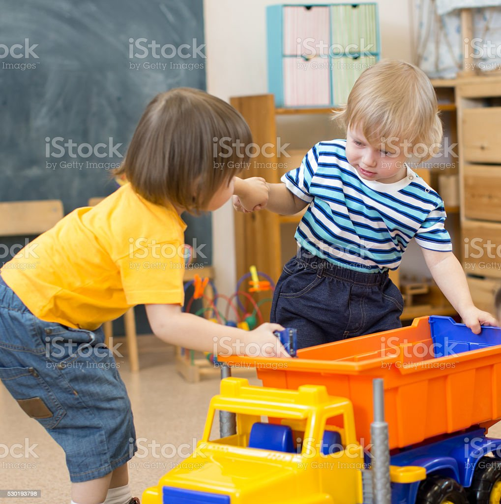 two kids conflict or struggling for toy truck in kindergarten stock photo