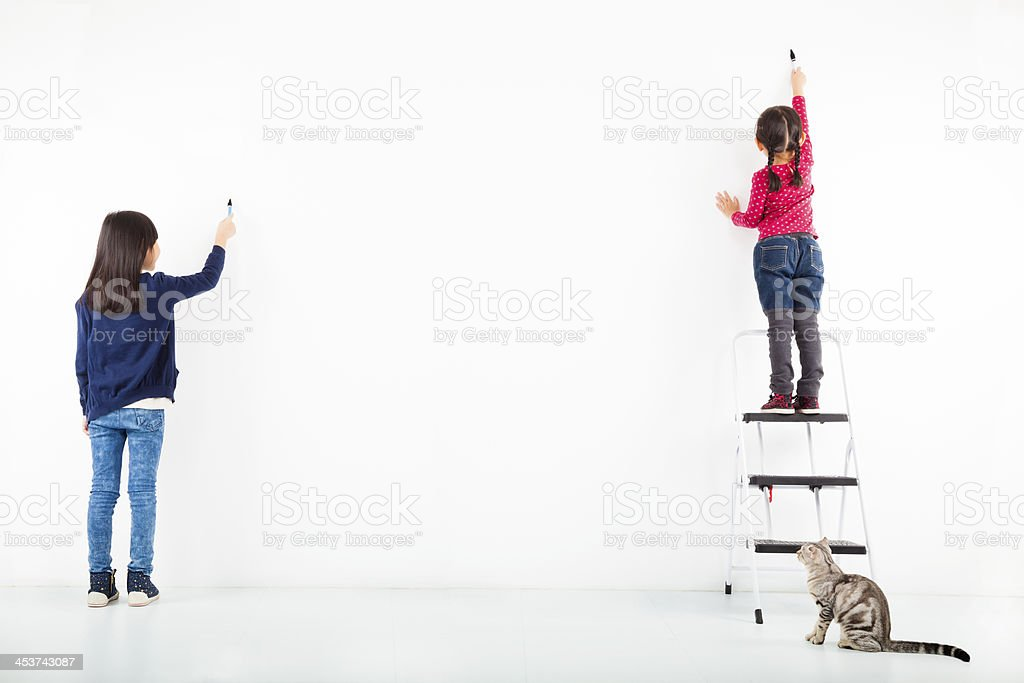 two kids drawing on the blank white wall stock photo