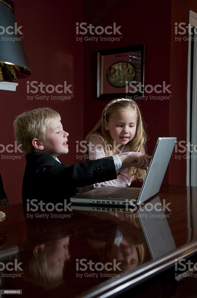 Two kids dressed in business attire looking at laptop stock photo