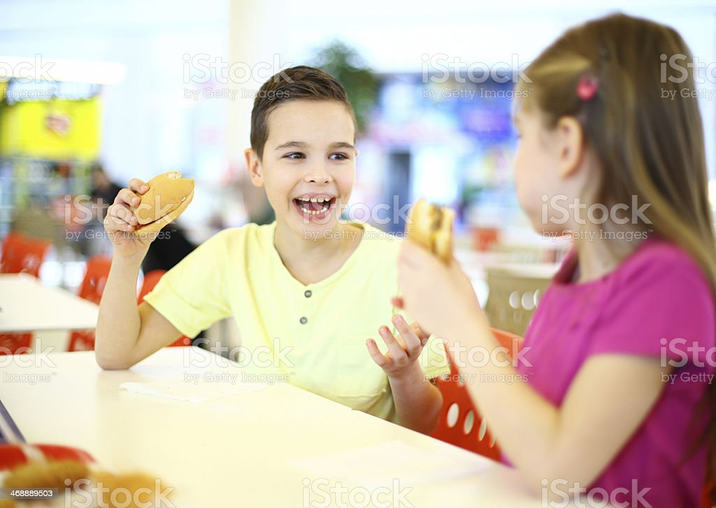Two kids eating burgers. royalty-free stock photo