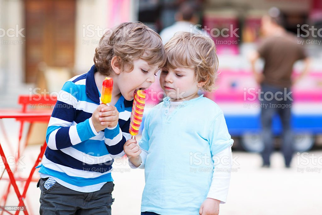 Two kids feeding each other with ice cream stock photo