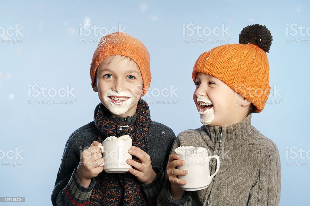 Two kids having fun in the snow drinking hot chocolate stock photo