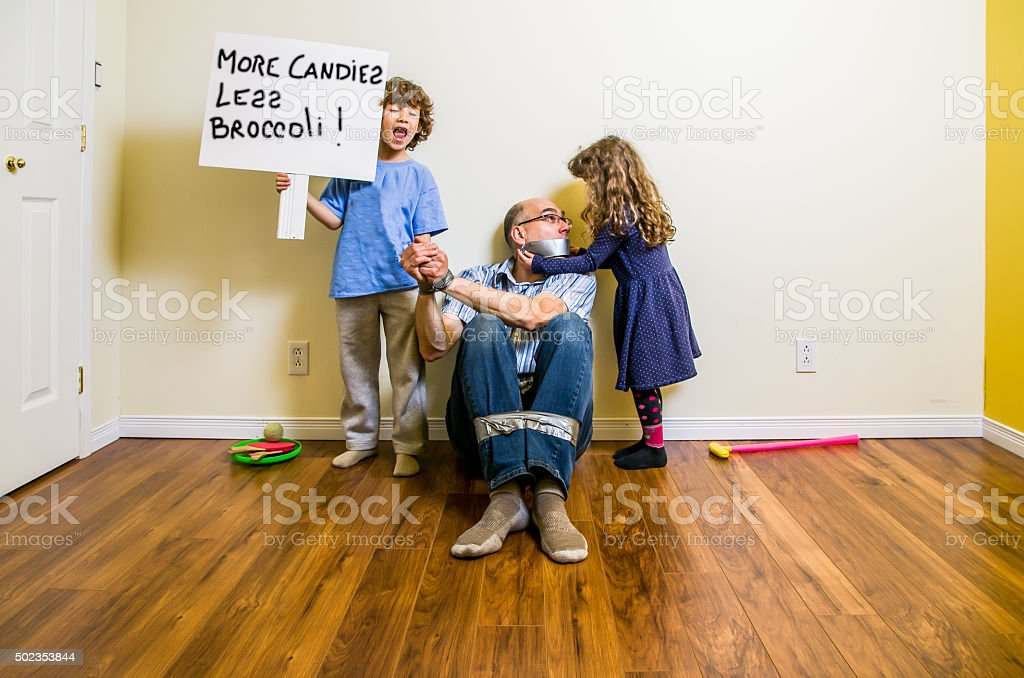 Two kids having their father as hostage with duct tape stock photo