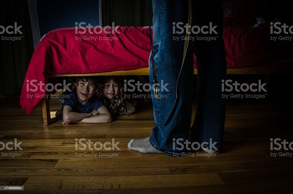 Two kids hidden under bed crying out of fear stock photo