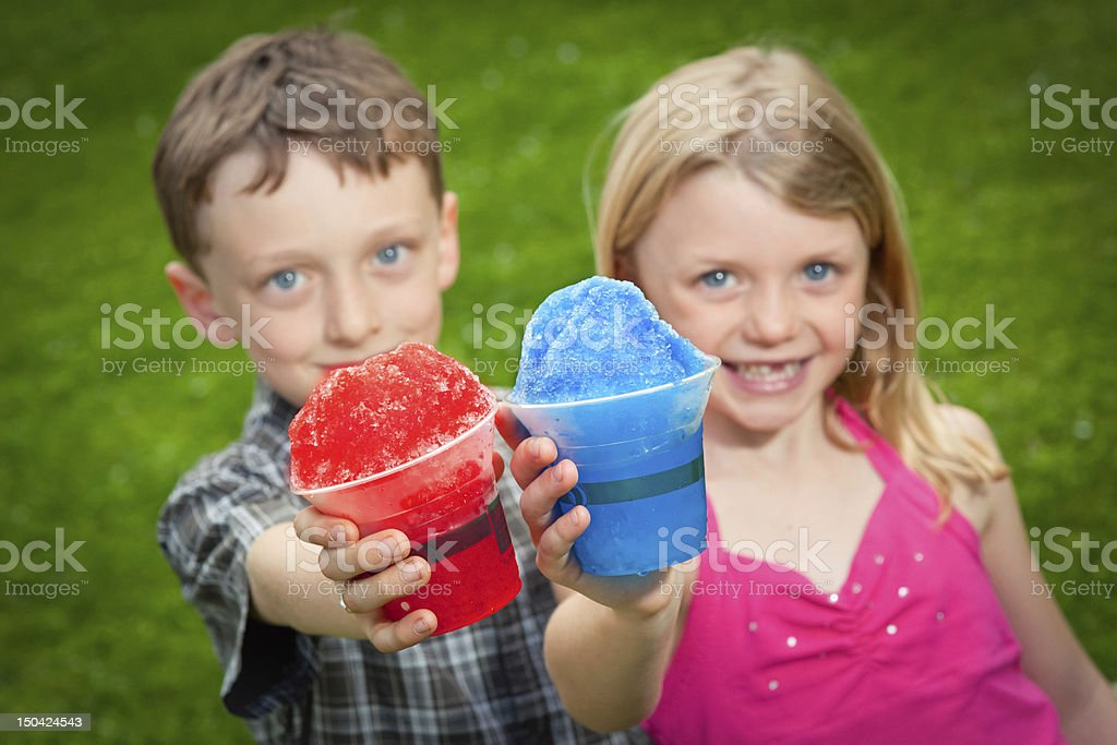 Two kids hold snow cones out to the camera. stock photo