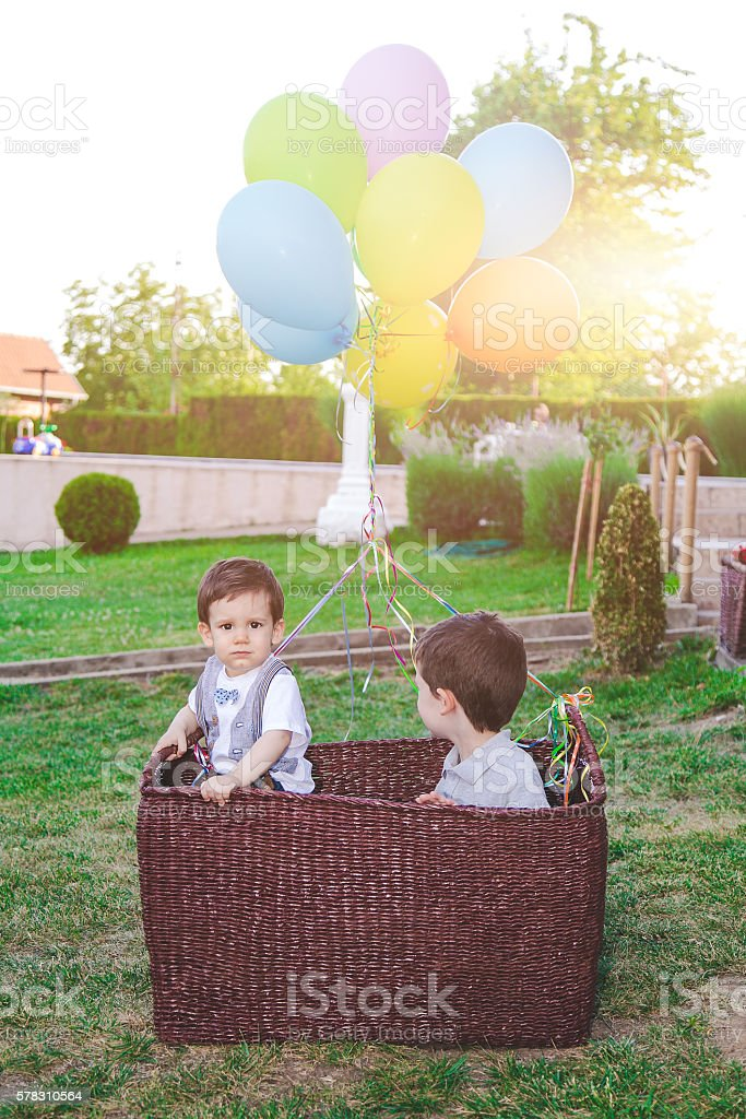 two kids in a basket with balloons stock photo