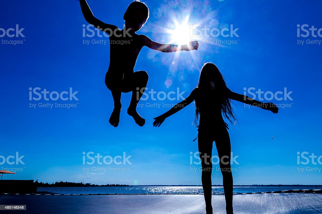 Two kids jumping on trampoline stock photo