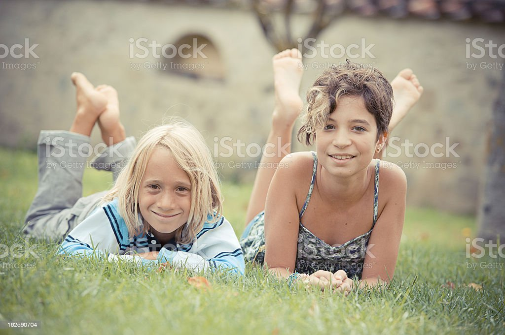 Two kids lying on top of grass royalty-free stock photo