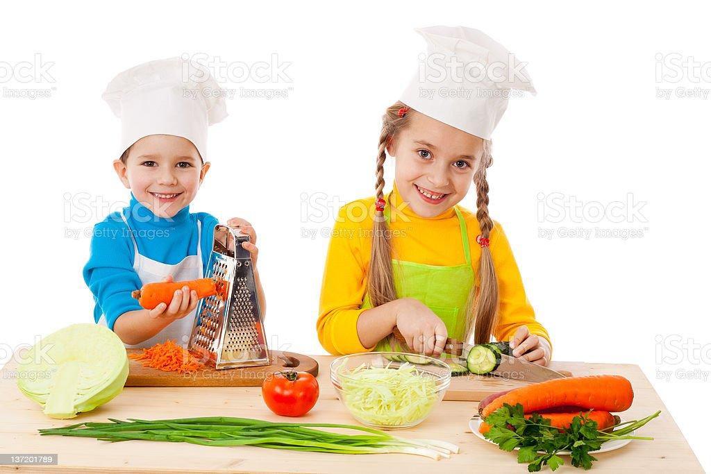 Two kids making salad stock photo