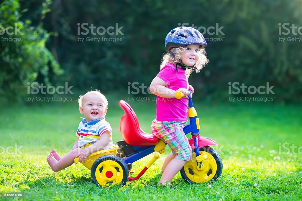 Two kids on a bike in the garden stock photo