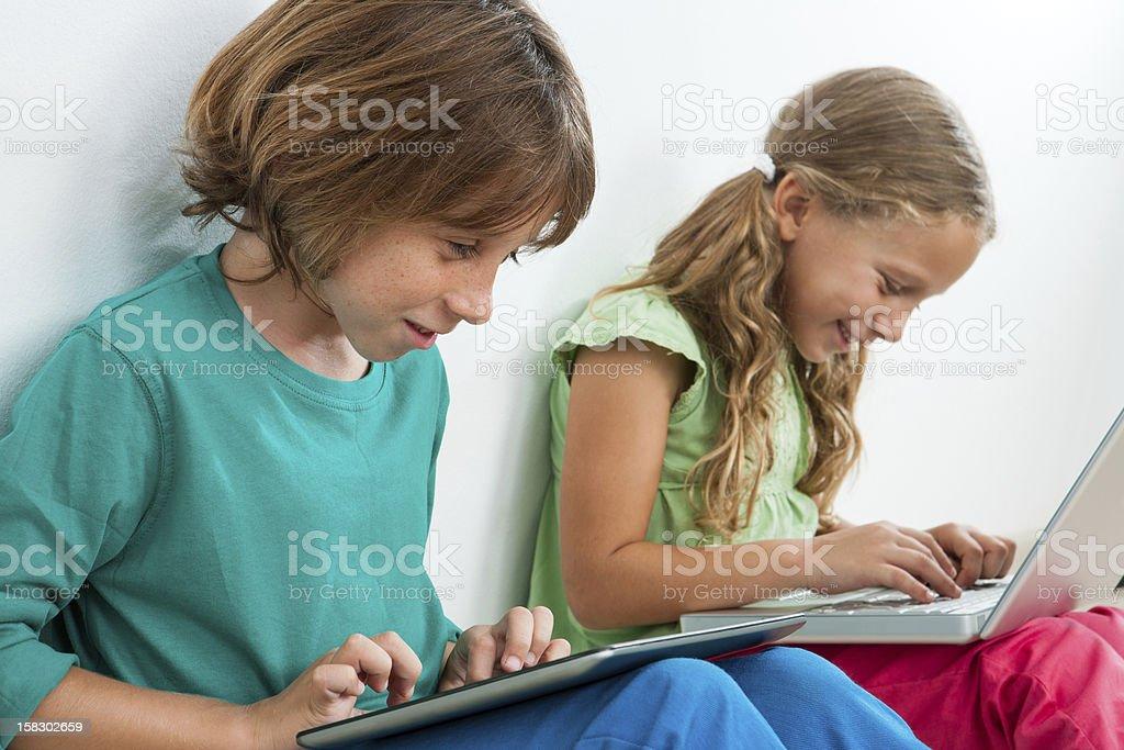Deux enfants jouant sur une tablette ou ordinateur portable. photo libre de droits