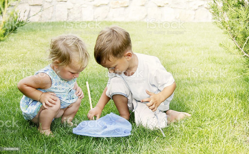 two kids playing with butterfly net royalty-free stock photo