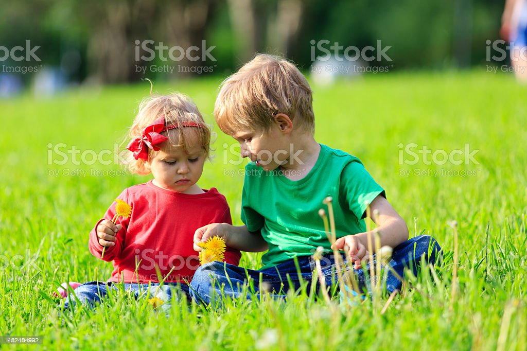 Two kids playing with dandelions on green grass stock photo