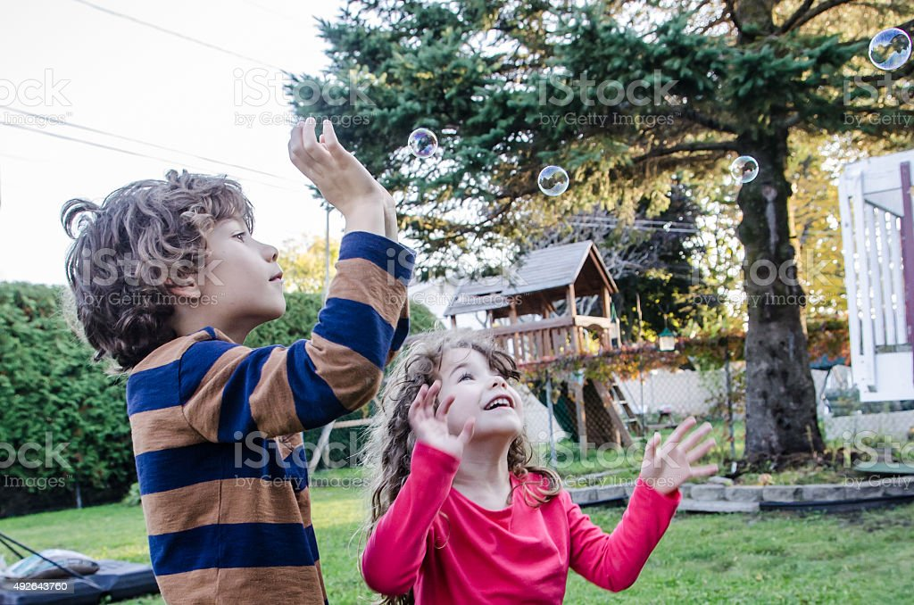 Two kids playing with soap bubble outside stock photo