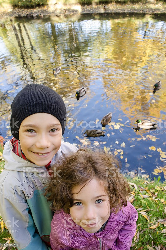 Two kids posing with ducks behind stock photo