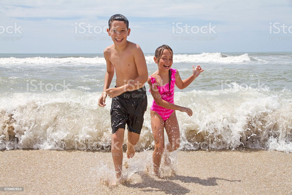 Two kids running from the sea stock photo