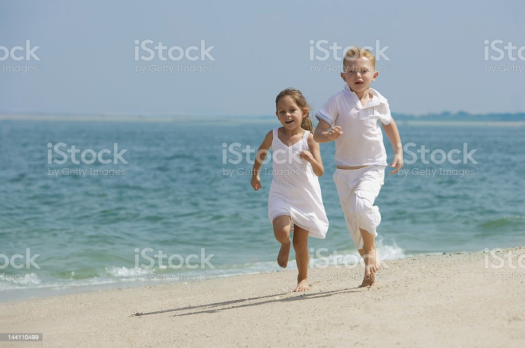two kids running on beach royalty-free stock photo