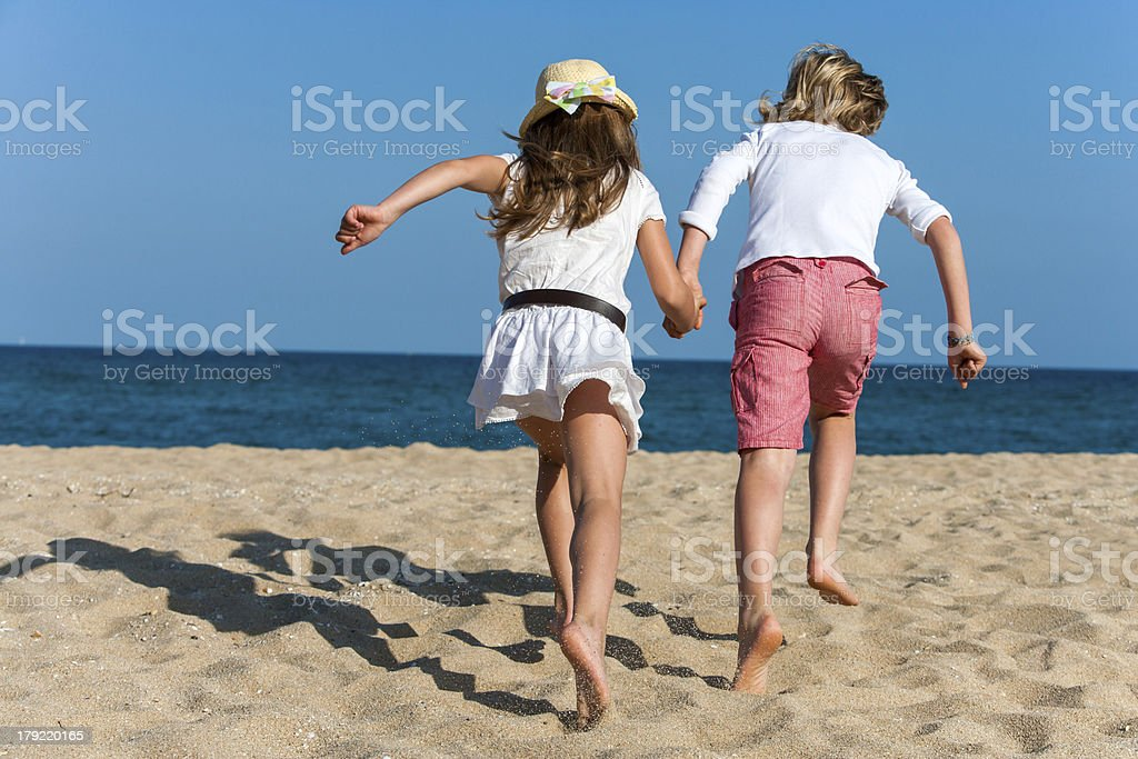 Two kids running together outdoors. royalty-free stock photo