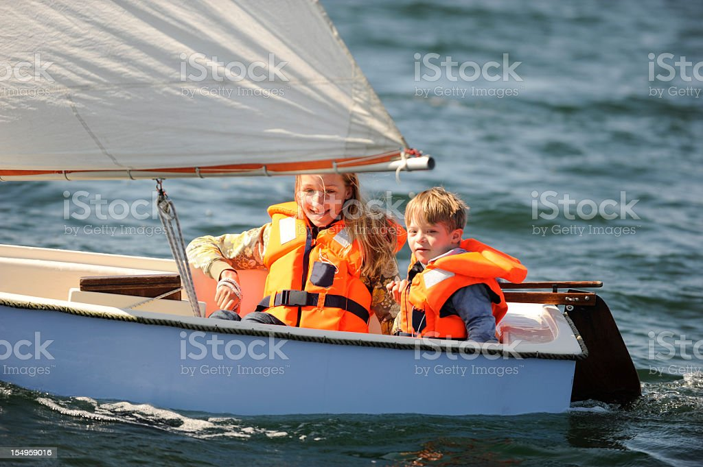 Two kids sailing in small vessel stock photo