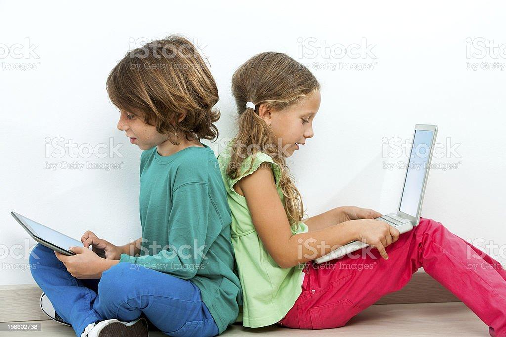 Deux enfants faire des rencontres grâce à un ordinateur portable et une tablette. photo libre de droits