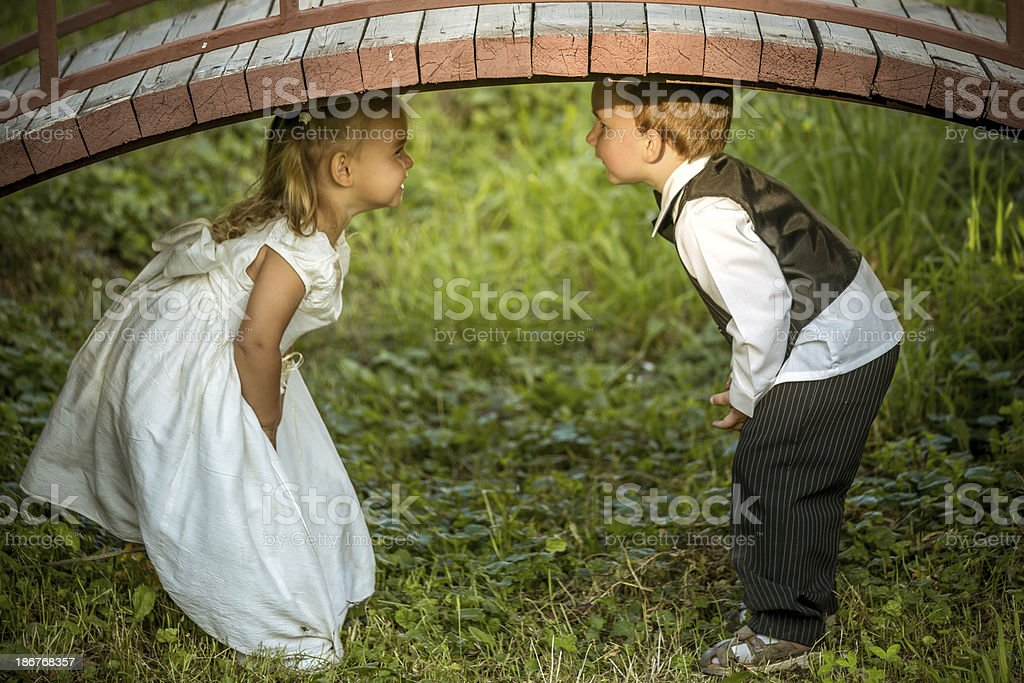 Two kids under ornamental bridge royalty-free stock photo