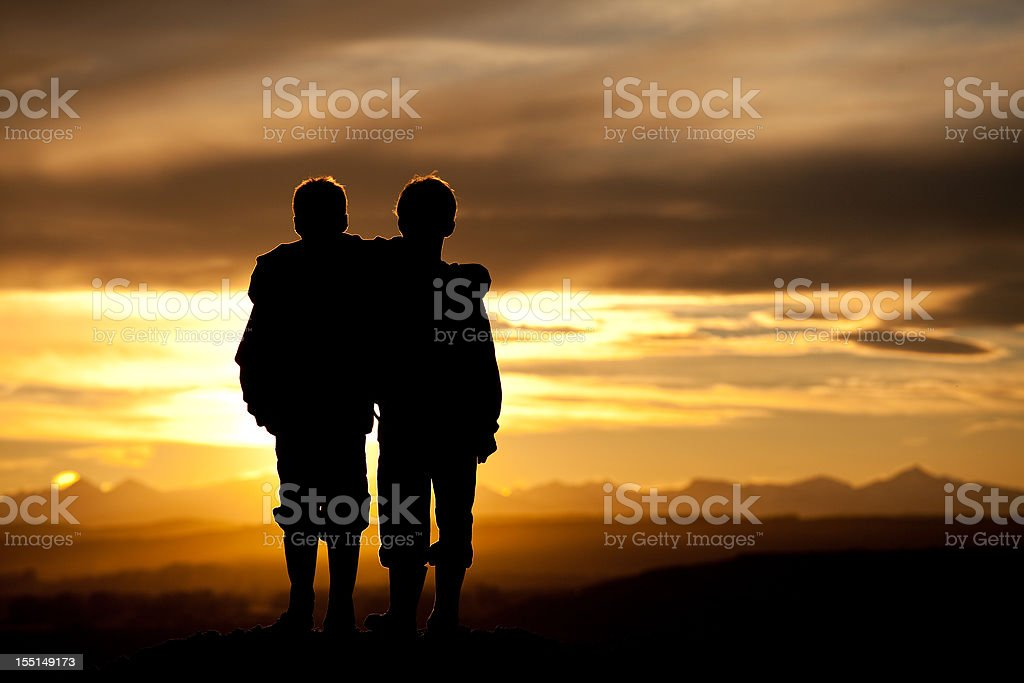 Two kids watching the sunset over horizon royalty-free stock photo