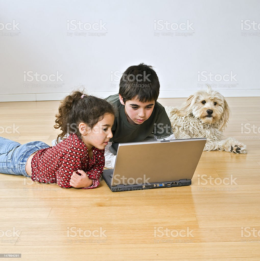 two kids with laptop computer and a dog royalty-free stock photo
