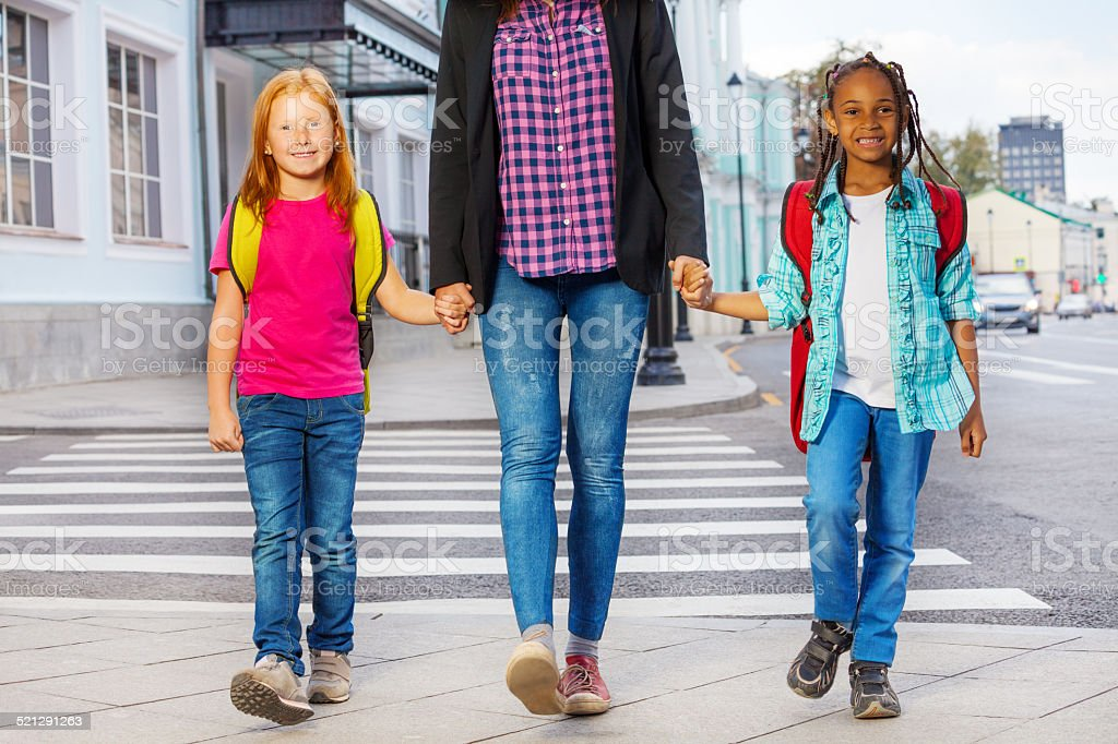 Two kids with woman walking on the street stock photo