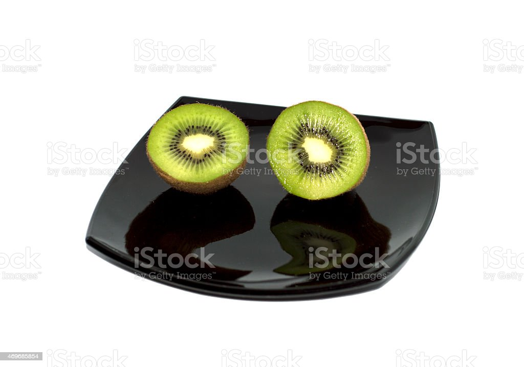 two kiwis on a black plate, the top view stock photo