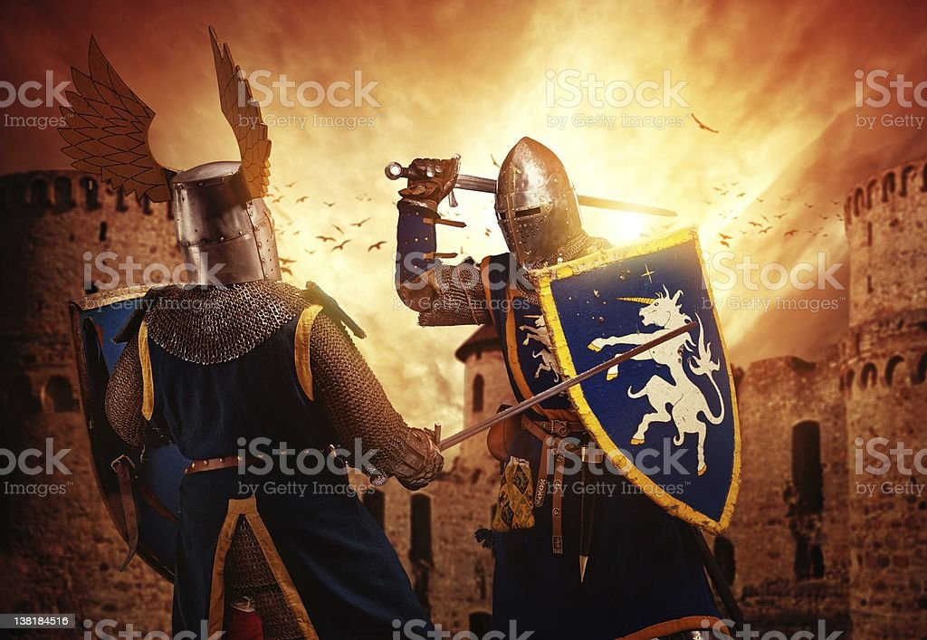 Two knights fighting against medieval castle. stock photo