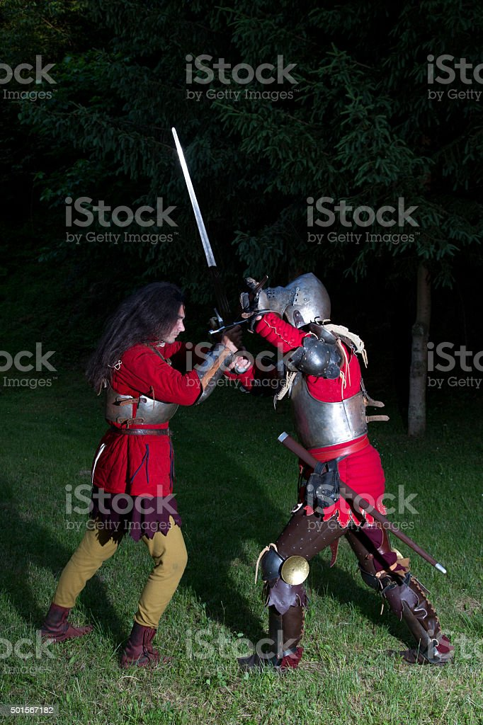 Two Knights in Battle in Dark Forest stock photo