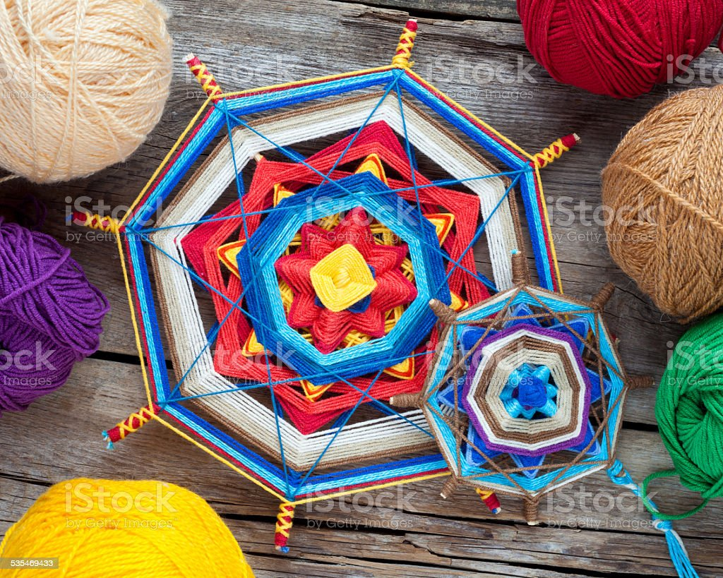 Two knitted tibetan mandala from threads and yarn on wooden rustic...
