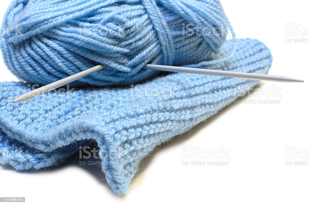 Two knitting needles, woollen yarn clew and cloth. royalty-free stock photo