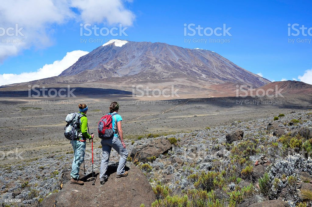 Two ladies hiking Mt Kilimanjaro on a sunny clear day stock photo