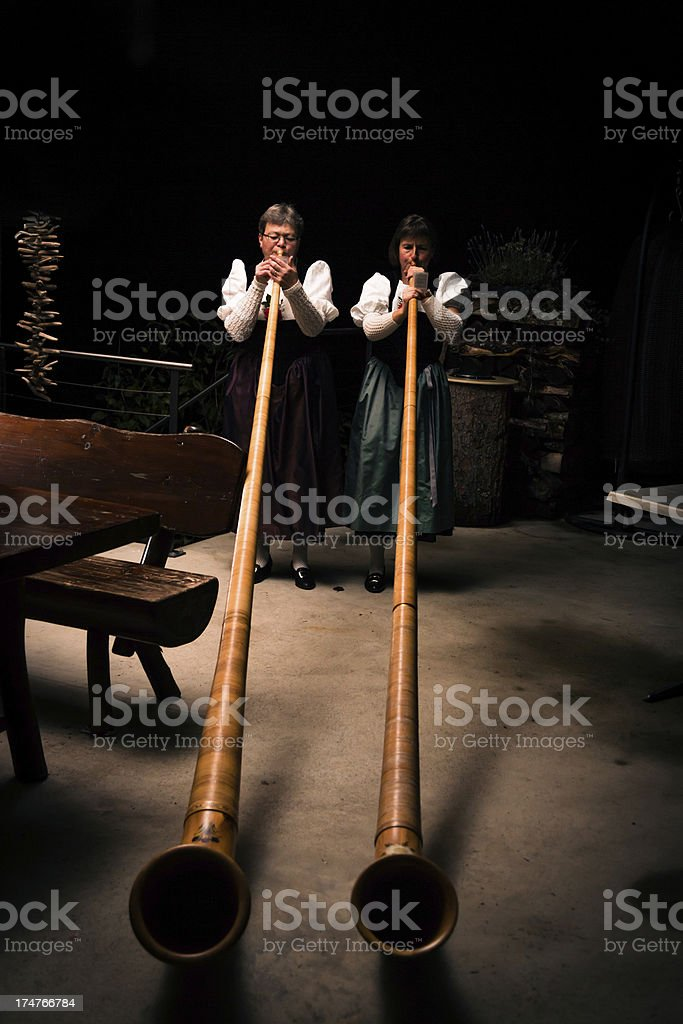 two ladies playing the alpenhorn stock photo
